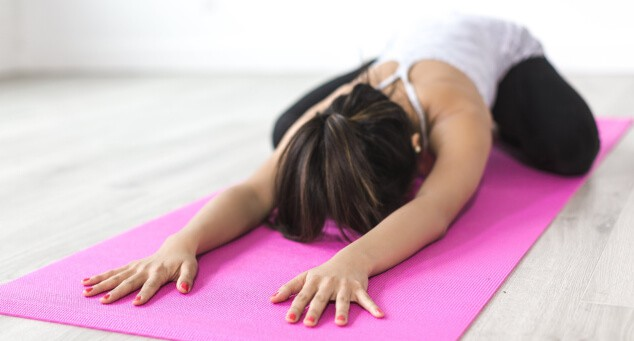 A Woman Practising Childs Post In Yoga On Pink Mat
