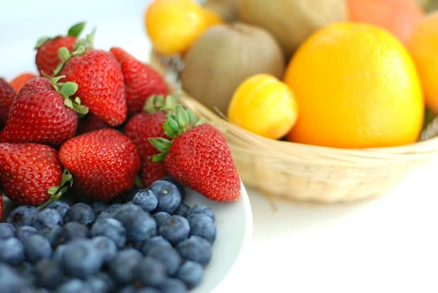 What is IBS? | Strawberries, blueberries, oranges and kiwis in bowls.