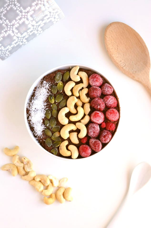 Overhead shot of paleo oatmeal topped with raspberries and cashews