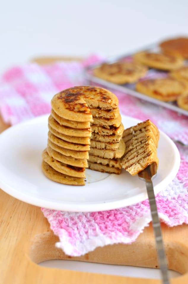 A stack of Healthy Peanut Butter Banana Pancakes with a big wedge cut out