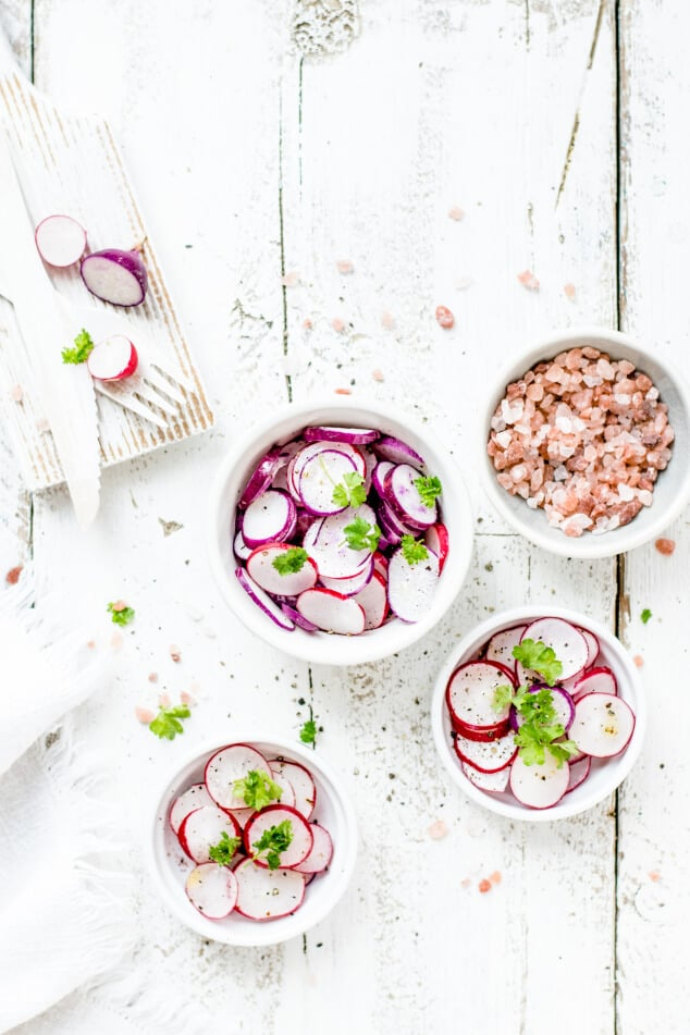 Bowls of sliced radishes on a light wooden background