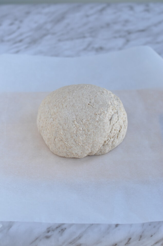 A ball of dough on parchment paper.