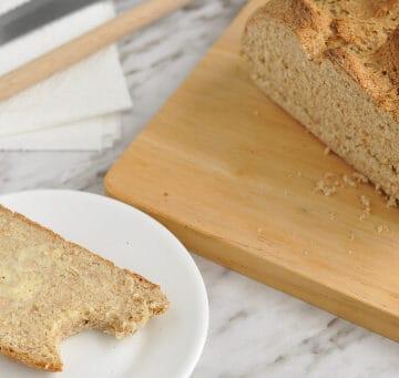 A chopping board with a loaf of easy Irish soda bread on it.