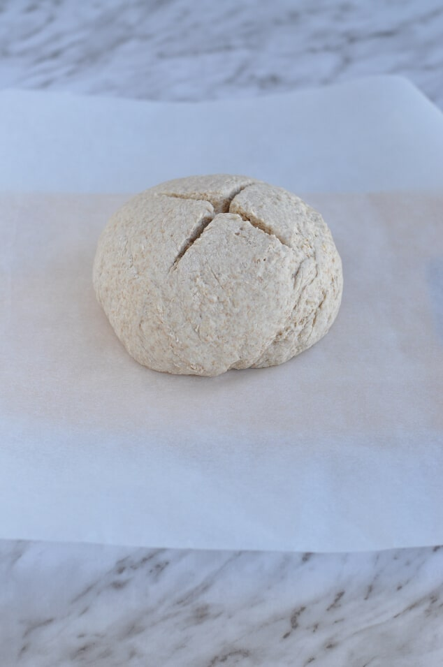 A ball of dough with a cross sliced into the top.