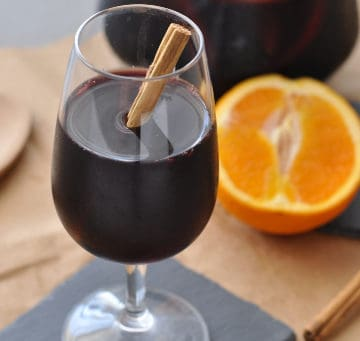 A glass of red wine fall sangria next to a sliced orange, cinnamon stick and wooden spoon