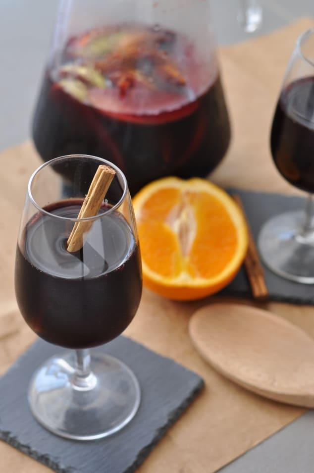 A glass of red wine fall sangria next to a sliced orange