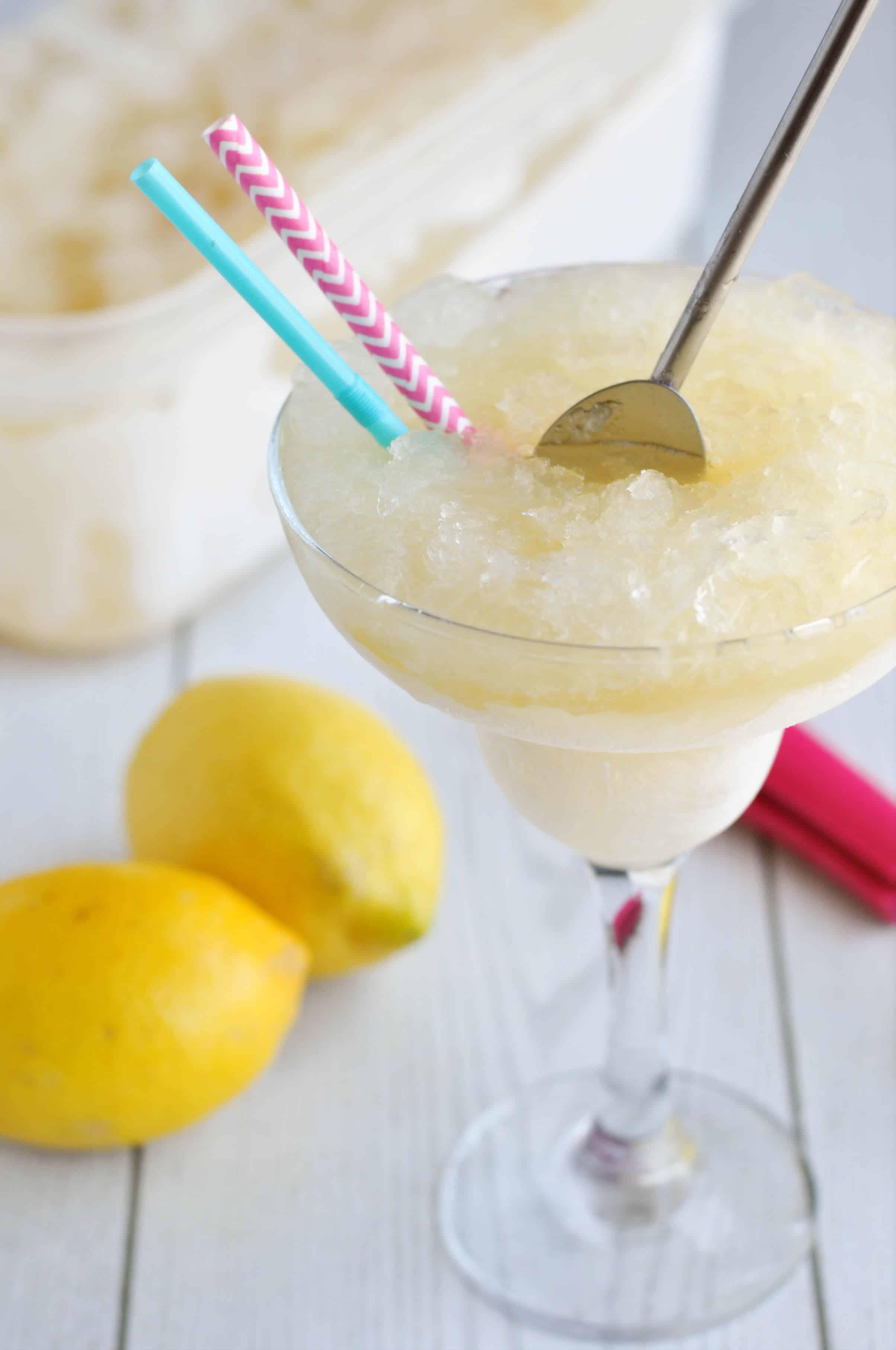A silver metal spoon stirring a glass of lemon vodka slush