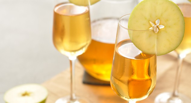 Two glasses and a jug filled with caramel apple sangria