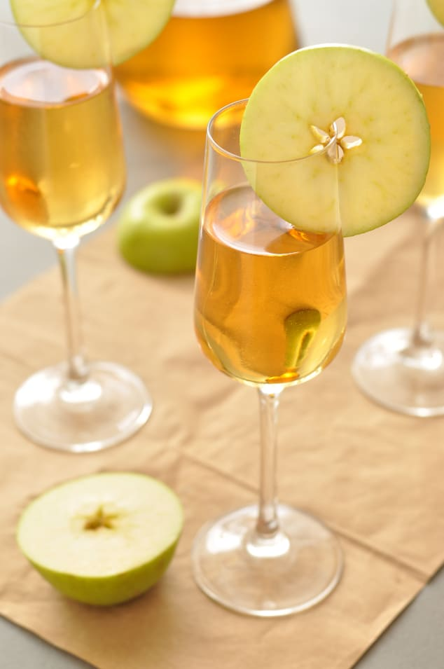 Three glasses of caramel apple sangria on brown paper next to a halved apple