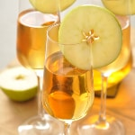 A close-up shot of three glasses of caramel apple sangria decorated with apple slices