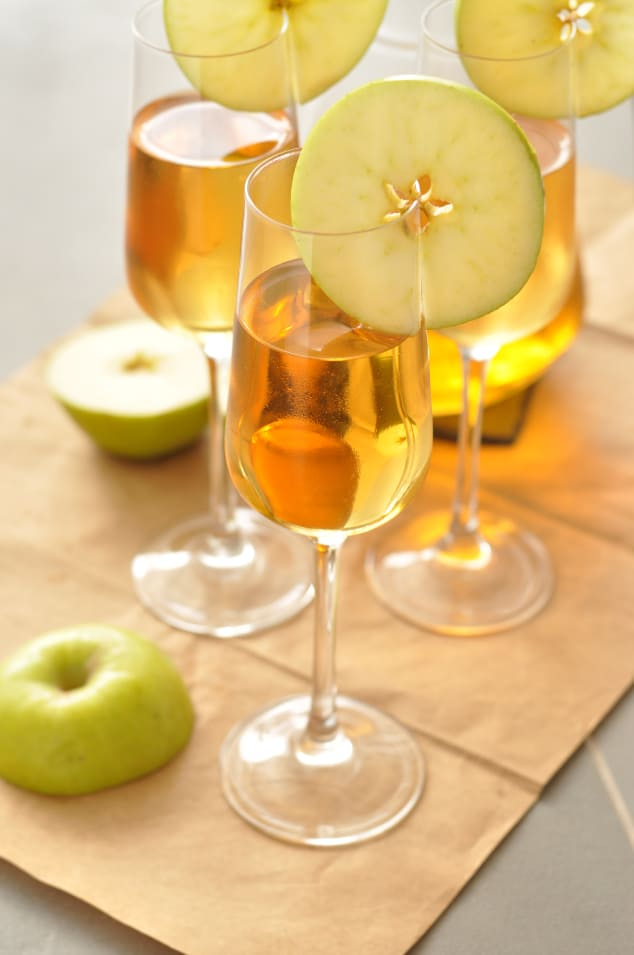 Three glasses of caramel apple sangria next to a halved apple