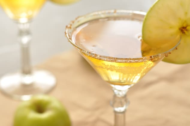 A close-up shot of a caramel apple martini on brown paper