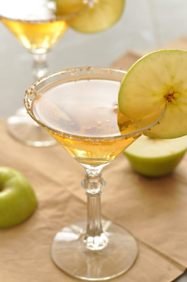 Caramel apple martinis next to two halves of an apple