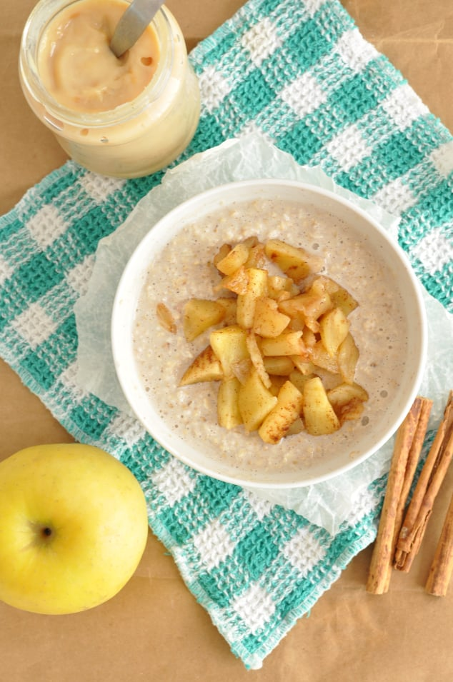 A bowl filled with oatmeal topped with apples
