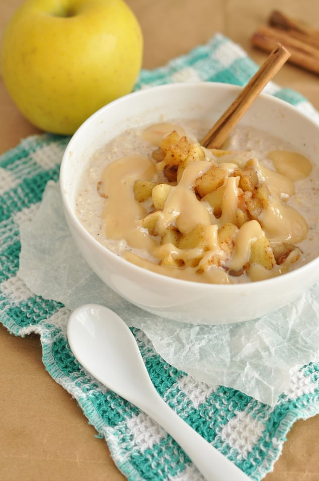 A bowl of caramel apple pie overnight oats next to a spoon and cinnamon sticks