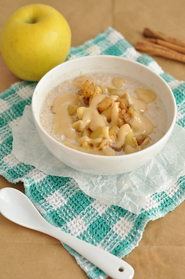 A bowl of caramel apple pie overnight oats next to an apple, cinnamon stick and a spoon