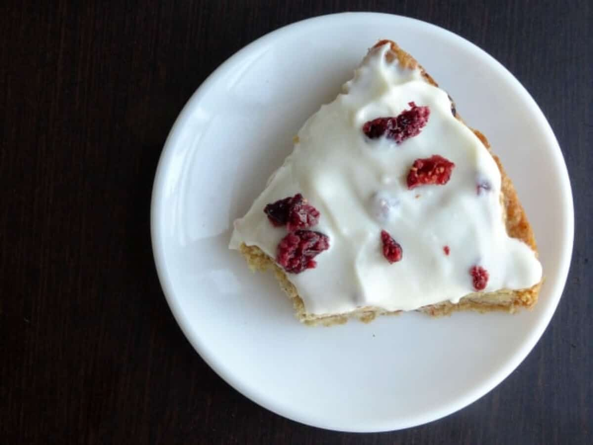 A slice of skinny Starbucks Cranberry Bliss Bar on a plate with a bite taken out.