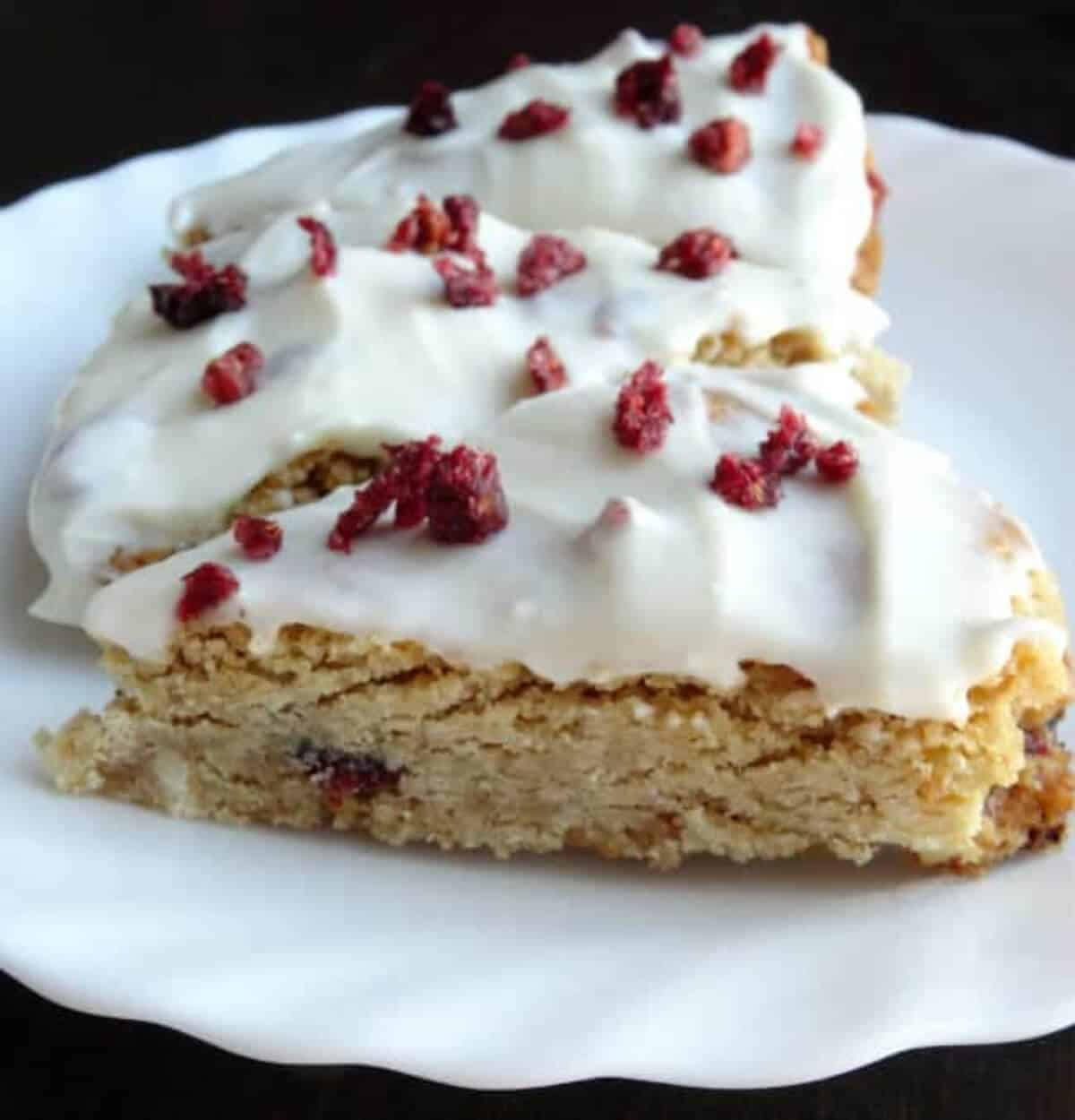 Three Copycat Starbucks Cranberry Bliss Bars lined up on a white plate.