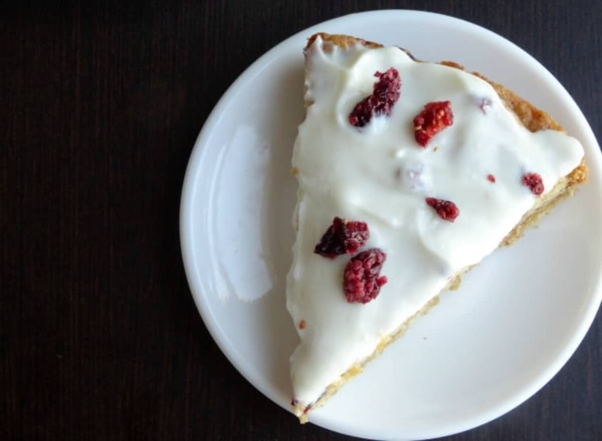 A triangular blondie with white icing and red cranberries.