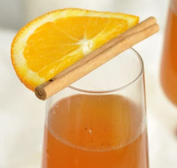 Top of a glass of mulled white wine with an orange slice and cinnamon stick