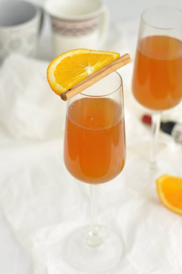 A single glass of white mulled wine with an orange segment and cinnamon stick balanced on top