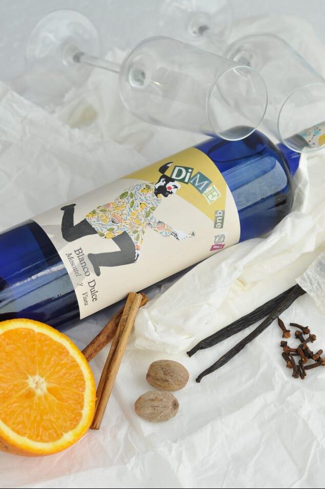 Bottle of wine next to an orange, cinnamon sticks, vanilla pods, nutmeg and cloves