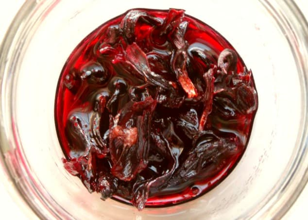 Overhead shot of hibiscus syrup and hibiscus flowers