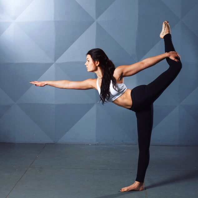 A woman in dark yoga clothes doing the dancer pose in front of a blue background