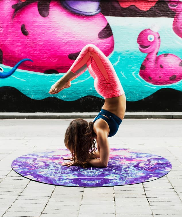 Woman doing a complicated yoga pose in front of a colourful background
