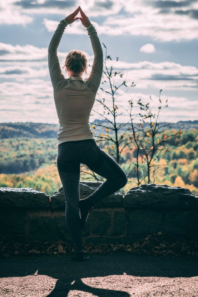 A woman doing the tree yoga pose in front of a scenic background