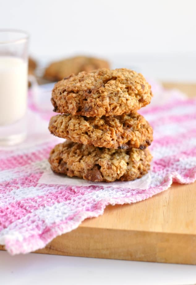 3 healthy chocolate chip oatmeal cookies stacked in front of a glass of milk