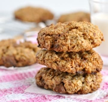 3 healthy chocolate chip oatmeal cookies in front of a glass of milk