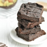Four healthy vegan brownies stacked on a plate