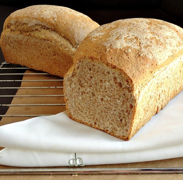 2 healthy whole wheat bread loaves on a wire rack