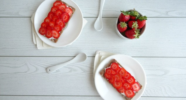 Healthy Strawberry Cheesecake Breakfast Toasts Recipe. Always wake up with a sweet tooth first thing in the morning? Then you NEED this quick, simple and healthy recipe! A whole wheat cracker slathered in a low calorie cheesecake-like spread, topped with fresh strawberries. I never knew I could eat cheesecake for breakfast and still be healthy!