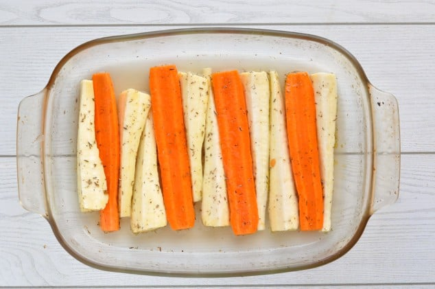 Raw carrots and parsnips in a glass baking tray