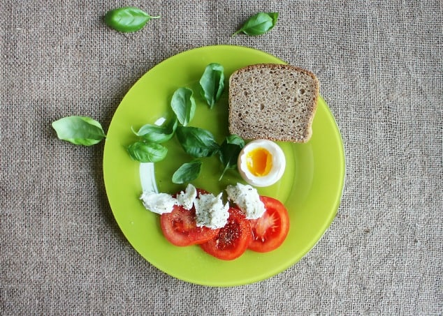 Green plate with toast, eggs and tomatoes