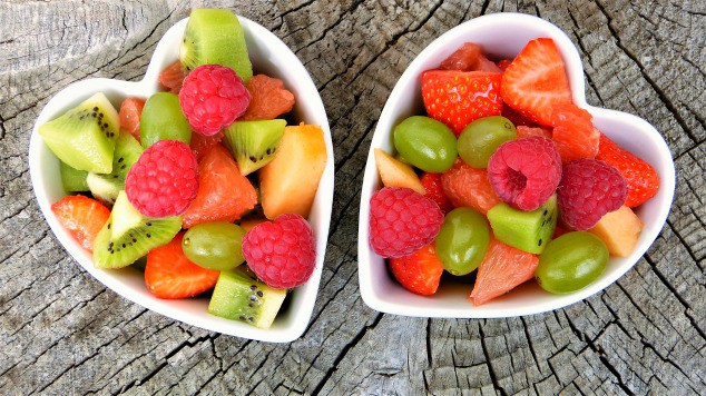 Heart-shaped bowls filled with fruits.