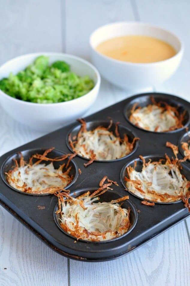 Baked hash browns in a black muffin tin
