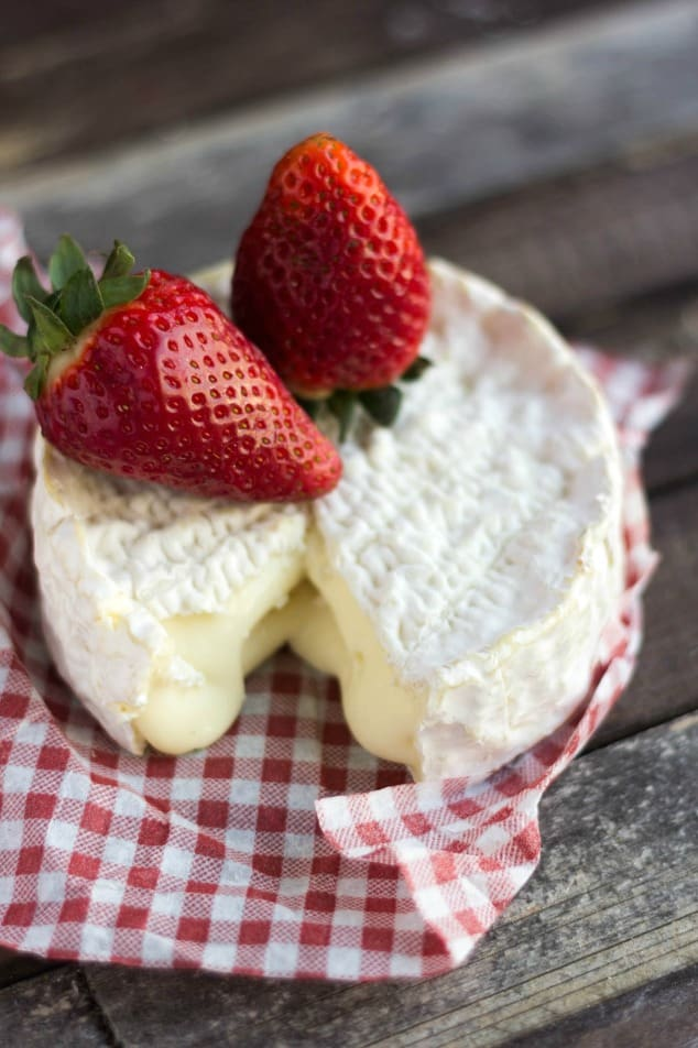 A round of Camembert cheese with strawberries