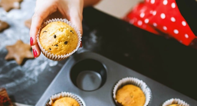 A woman picking up a low FODMAP chocolate chip muffin