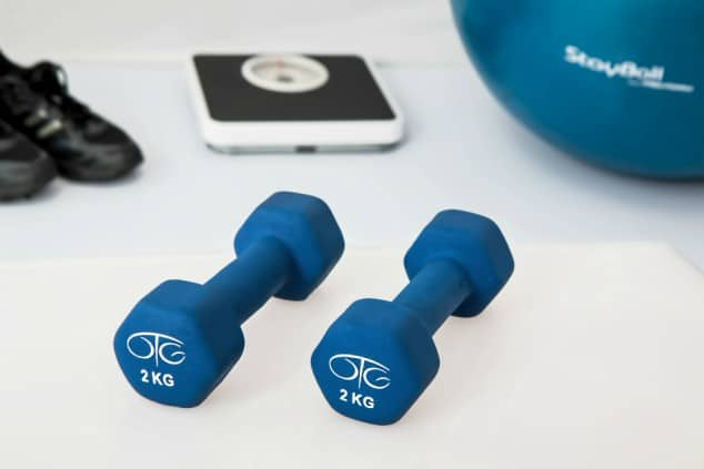 A pair of small blue dumbbells next to a set of scales