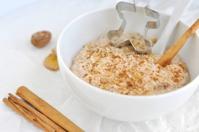 A bowl of Healthy Gingerbread Overnight Oats decorated with a gingerbread man cookie cutter and cinnamon stick
