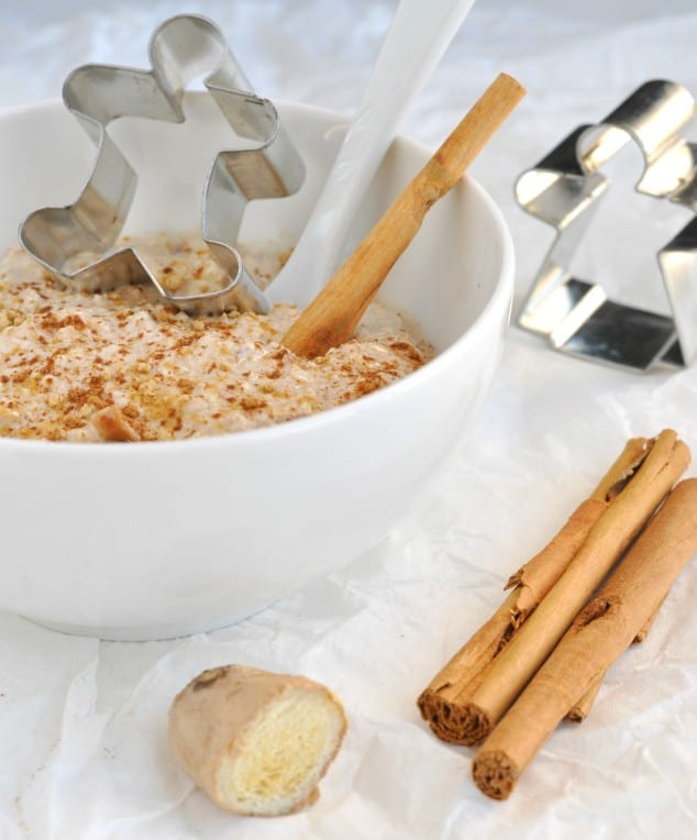 A bowl of Healthy Gingerbread Overnight Oats surrounded by cinnamon sticks