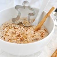 A bowl of Healthy Gingerbread Overnight Oats with a cinnamon stick and ground cinnamon
