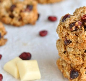 Delicious white chocolate cranberry cookies next to squares of white chocolate