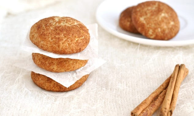 A stack of healthy snickerdoodles with a plate of cookies in the background
