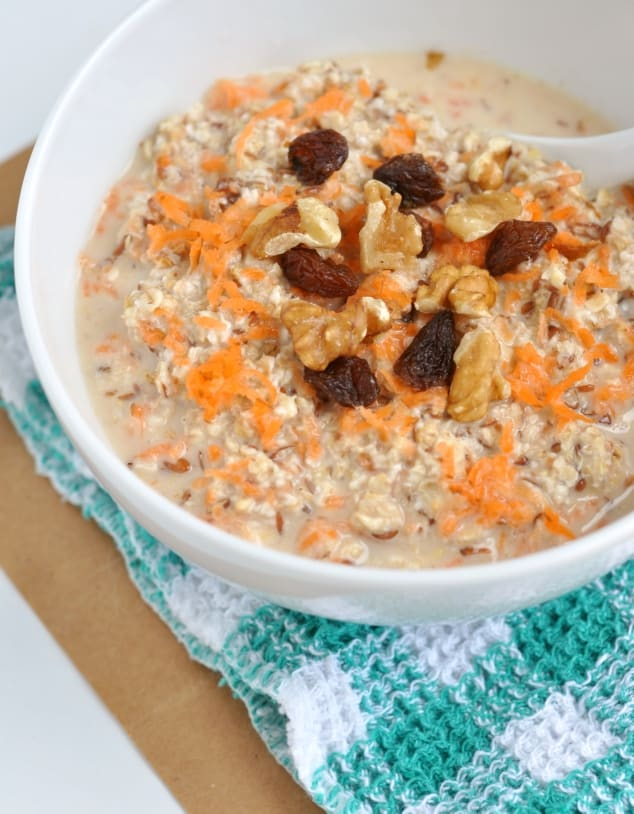 A bowl of carrot cake overnight oats topped with shredded carrot, raisins and walnuts