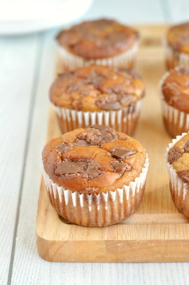 Two rows of healthy banana bread muffins on a wooden board