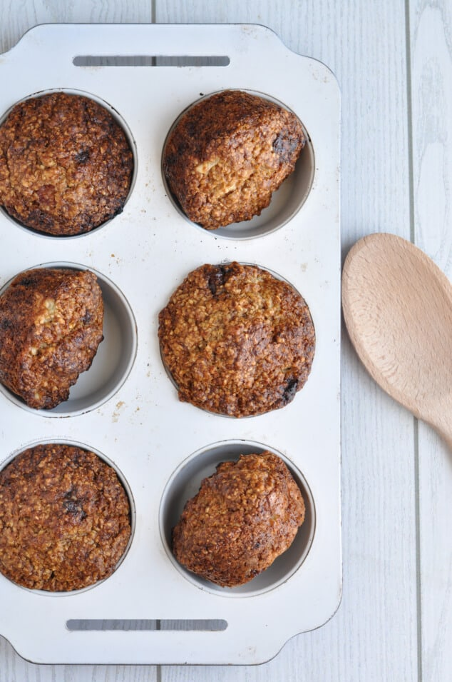 Healthy Oat Bran Muffins with Chocolate Chips in a muffin tin next to a wooden spoon